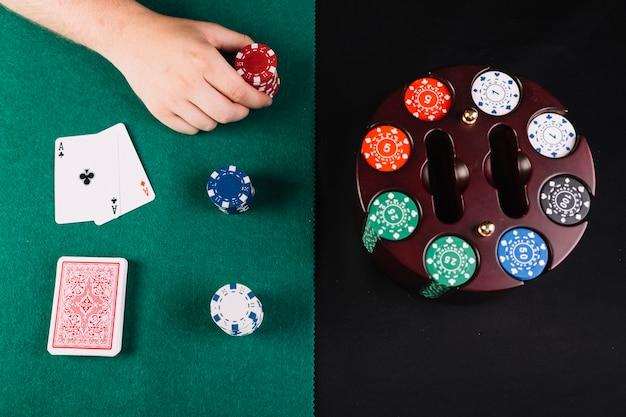 Vue grand angle d'une personne jouant au poker près d'un jeu de puces dans un étui de carrousel Photo gratuit
