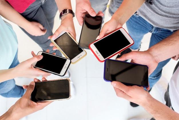 Vue grand angle de personnes utilisant un téléphone portable Photo gratuit