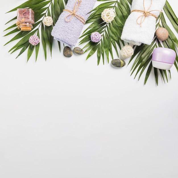 Vue grand angle sur les pierres du spa; les serviettes; crème hydratante; gommage bouteille et feuilles sur fond blanc Photo gratuit