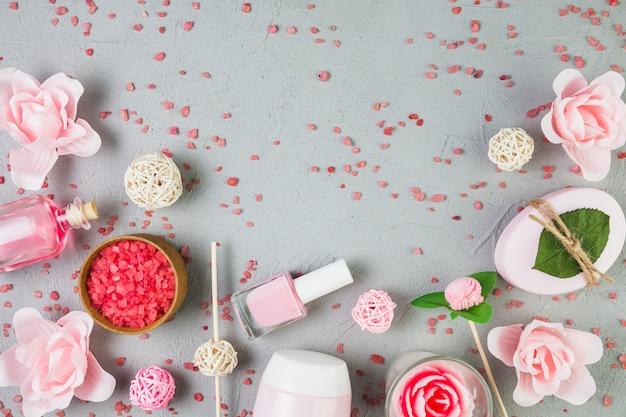 Vue grand angle de produits de beauté avec des fleurs sur fond gris Photo gratuit