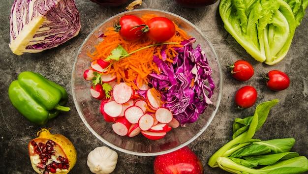 Vue grand angle de salade fraîche dans un bol en verre entouré de fruits et légumes Photo gratuit