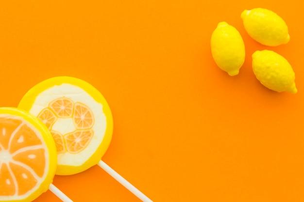 Vue grand angle de sucettes d'agrumes frais et bonbons au citron sur fond orange Photo gratuit