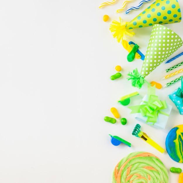 Vue grand angle de sucettes; des sucreries; bougies; souffleur de corne de fête; sifflet et chapeau sur fond blanc Photo gratuit