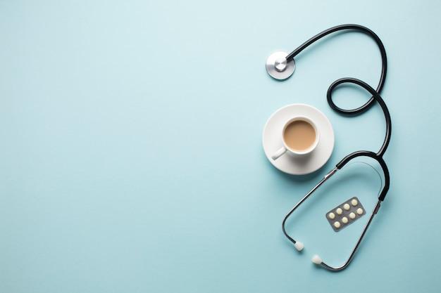 Vue grand angle de la tasse à café; stéthoscope et médicament en blister sur fond bleu Photo gratuit