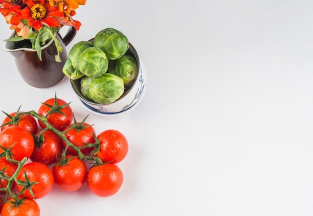 Vue grand angle de tomates juteuses; choux de bruxelles et fleurs sur fond blanc Photo gratuit