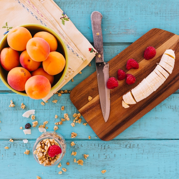 Vue grand angle de tranches de banane; des fraises; pêche et avoine sur fond en bois bleu Photo gratuit