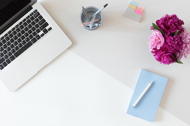 Vue d'en haut du milieu de travail femme avec clavier d'ordinateur, ordinateur portable, bouquet de fleurs de pivoine rose et téléphone portable, poser à plat. Photo Premium
