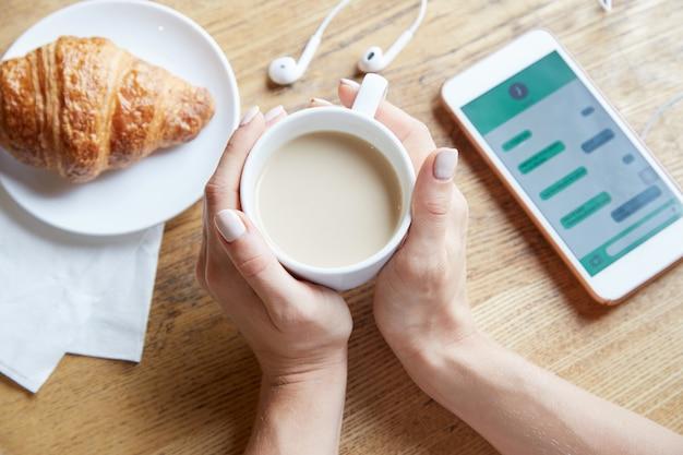 Vue d'en haut des mains féminines tenant une tasse de café Photo gratuit