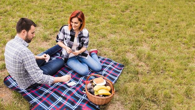 Vue haut, de, sourire, jeune couple, jouer, à, cartes, sur, couverture, à, pique-nique Photo gratuit