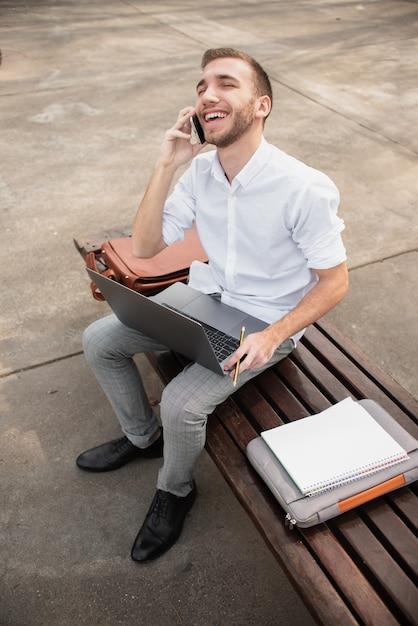Vue haute d'un étudiant parle au téléphone Photo gratuit