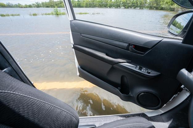 Vue à l'intérieur de la voiture, voiture conduisant à travers une autoroute inondée. Photo Premium