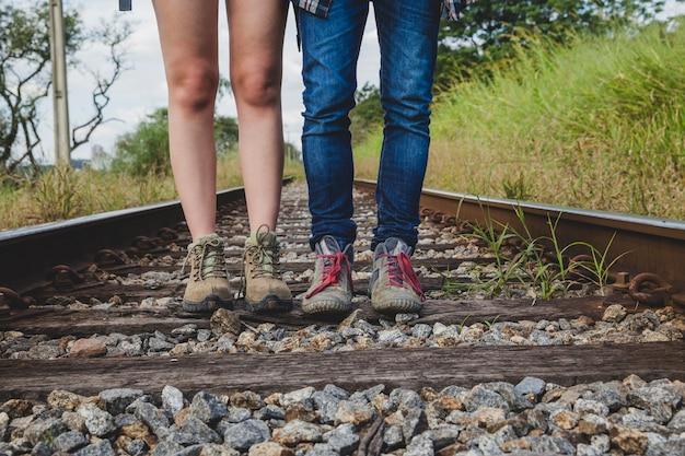 Vue en jambe du couple de randonneurs sur les voies ferrées Photo gratuit