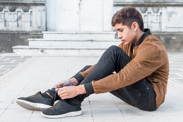 Vue latérale d'un adolescent assis à l'extérieur et attachant ses chaussures en dentelle Photo gratuit