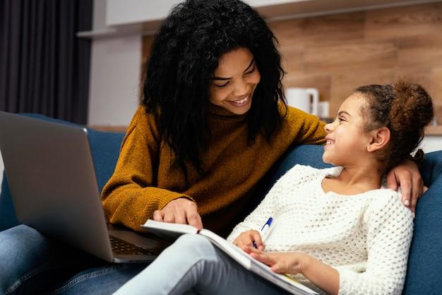 Vue Latérale D'une Adolescente Smiley Aidant La Petite Soeur Avec L'école En Ligne Photo gratuit