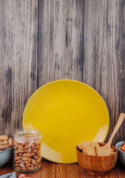 Vue Latérale D'amandes Dans Un Bocal En Verre Et Un Bol Avec Du Beurre D'arachide Avec Une Plaque En Céramique Jaune Sur La Table à Fond En Bois Photo gratuit