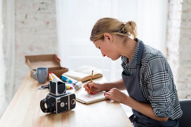 Vue latérale de l'artiste en tablier travaillant sur un bureau Photo gratuit
