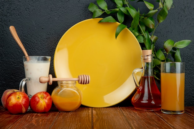 Vue Latérale D'une Assiette Jaune Vide Et De Nectarines Mûres Fraîches Avec Une Bouteille D'huile D'olive Photo gratuit