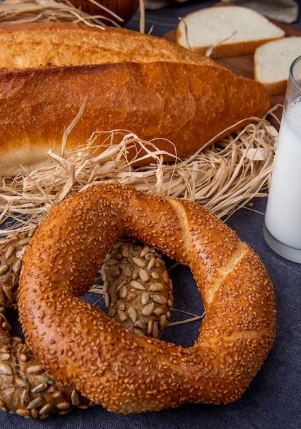 Vue Latérale Des Bagels Turcs Avec Baguette Sur Paille Sur La Surface Marron Photo gratuit