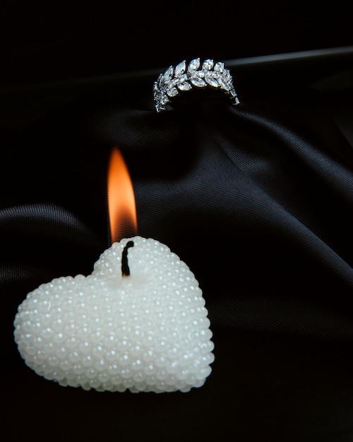 Vue Latérale D'une Bague En Argent Sterling Avec Des Diamants Et Avec Une Bougie Décorative En Forme De Cœur Sur Un Mur Noir Photo gratuit