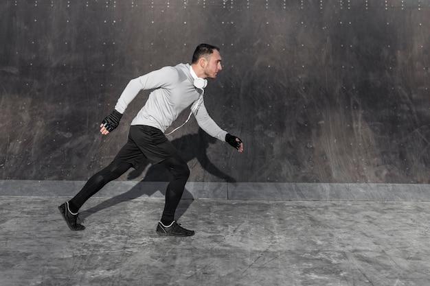 Vue latérale bel homme qui court à l'extérieur Photo gratuit