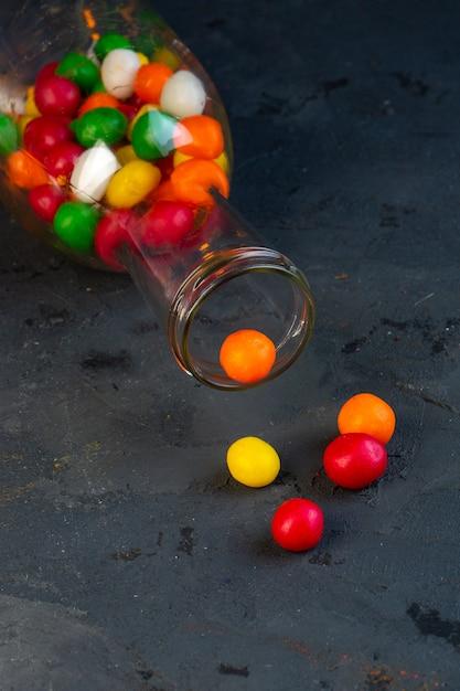 Vue Latérale De Bonbons Colorés Dans Une Bouteille En Verre Sur Fond Noir Photo gratuit