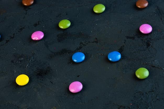 Vue Latérale De Bonbons Colorés Dispersés Sur Fond Noir Photo gratuit