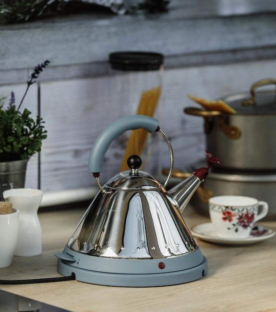 Vue Latérale D'une Bouilloire électrique Moderne Avec Sifflet Sur Une Table En Bois Dans La Cuisine Photo gratuit