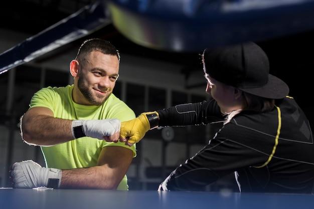 Vue Latérale Des Boxeurs Masculins Et Féminins Dans Une Bosse De Poing Photo gratuit