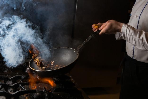 Vue Latérale Champignon Frire Avec De La Fumée Et Du Feu Et De L'homme Dans Le Poêle Photo gratuit