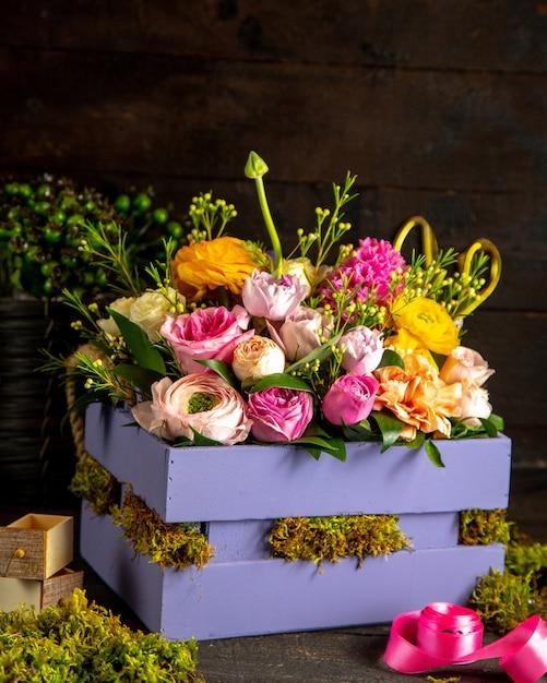 Vue Latérale De La Composition De Roses Roses Et Lilas Et De Fleurs De Renoncule Dans Une Boîte En Bois Photo gratuit