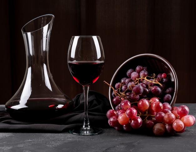 Vue Latérale De La Cruche Avec Du Vin Rouge Et Du Raisin Sur Horizontal Sombre Photo gratuit