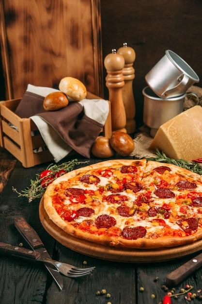 Vue Latérale Délicieuse Pizza Salée Avec Pepperoni Et Poivre Sur Le Tableau Noir Sur Le Fond En Bois Sombre, Vertical Photo Premium