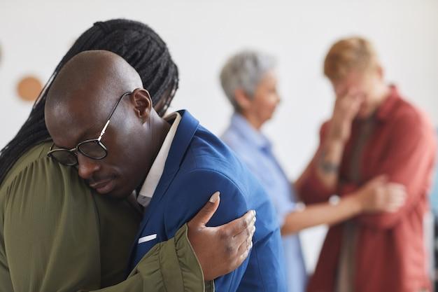 Vue Latérale à Deux Afro-américains Embrassant Pendant La Réunion Du Groupe De Soutien, S'entraider Avec Le Stress, L'anxiété Et Le Chagrin, Copy Space Photo Premium