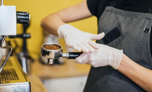 Vue Latérale Du Barista Avec Des Gants En Latex Préparer Du Café Pour La Machine Photo gratuit