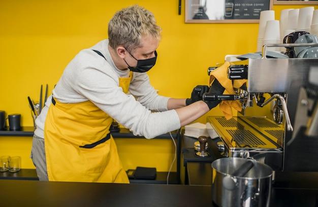 Vue Latérale Du Barista Masculin Avec Masque Médical Nettoyage Machine à Café Photo gratuit