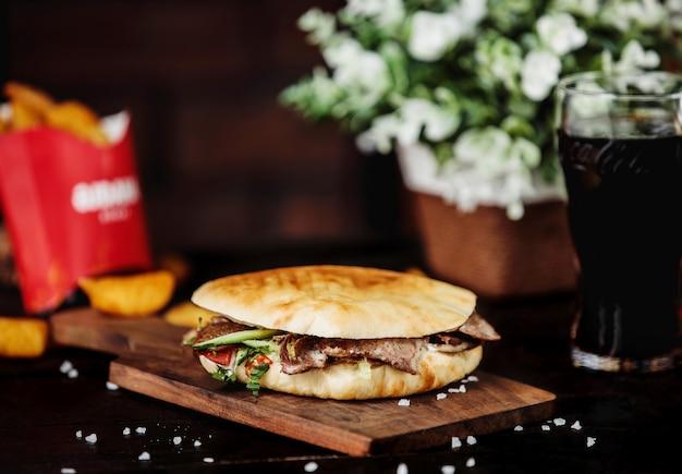 Vue Latérale Du Bœuf Doner Kebab Dans Du Pain Pita Et Sur Planche De Bois Photo gratuit