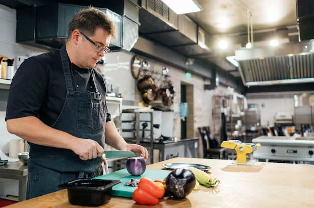 Vue Latérale Du Chef Masculin Couper Les Légumes Dans La Cuisine Photo Premium