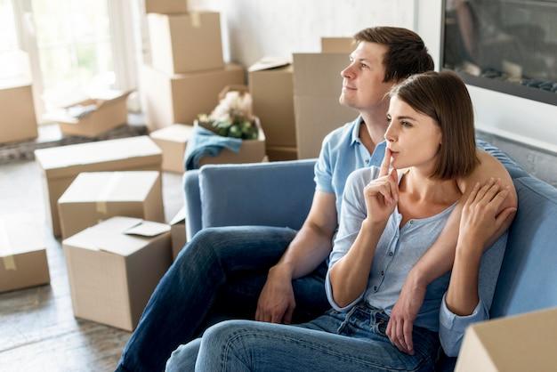 Vue Latérale Du Couple Sur Le Canapé Prépare Les Choses à Déménager Photo gratuit