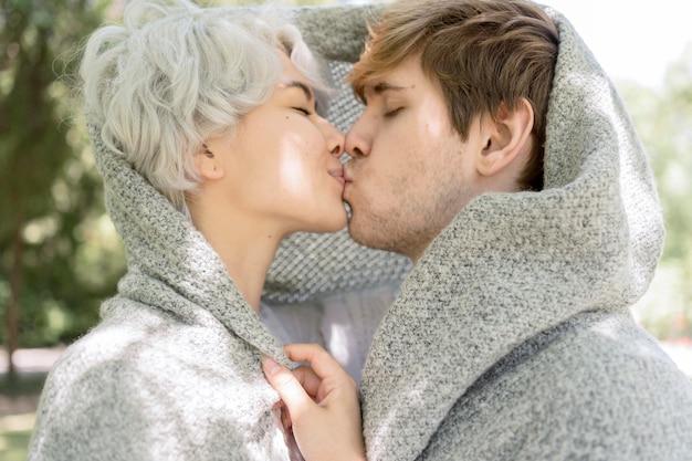 Vue Latérale Du Couple Couvert De Blanker S'embrasser à L'extérieur Photo gratuit
