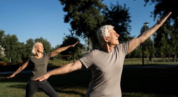 Vue Latérale Du Couple De Personnes âgées Pratiquant Le Yoga En Plein Air Photo Premium