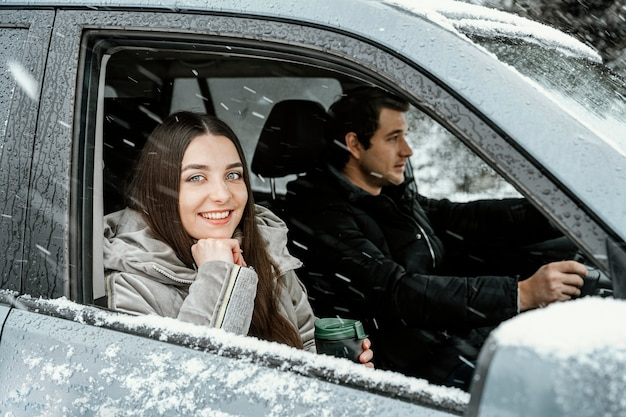 Vue Latérale Du Couple Smiley Dans La Voiture Lors D'un Road Trip Photo gratuit
