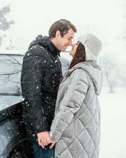 Vue Latérale Du Couple Smiley S'embrasser Dans La Neige Lors D'un Voyage Sur La Route Photo gratuit