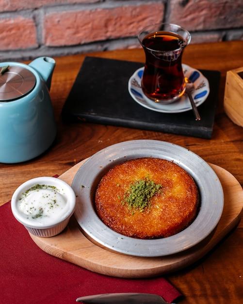 Vue Latérale Du Dessert Traditionnel Turc Kunefe Avec De La Poudre De Pistache Et Du Fromage Sur Une Table En Bois Photo gratuit
