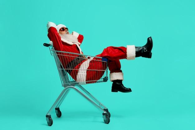 Vue Latérale Du Drôle De Père Noël Dans Des Lunettes De Soleil Noires Et Des Visages De Costumes. Vieil Homme S'amuser, Assis Et Se Détendre Dans Le Panier Photo gratuit