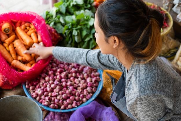 Vue Latérale Du Haut D'un Maraîcher Asiatique Tenant Une Carotte Dans Un Sac à Un étal De Légumes Photo Premium
