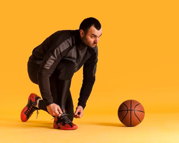 Vue Latérale Du Joueur De Basket-ball Masculin Attachant Les Lacets De Chaussures Avec Ballon Et Copie Espace Photo gratuit