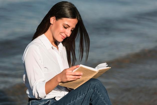 Vue Latérale Du Livre De Lecture De Femme à La Plage Photo gratuit