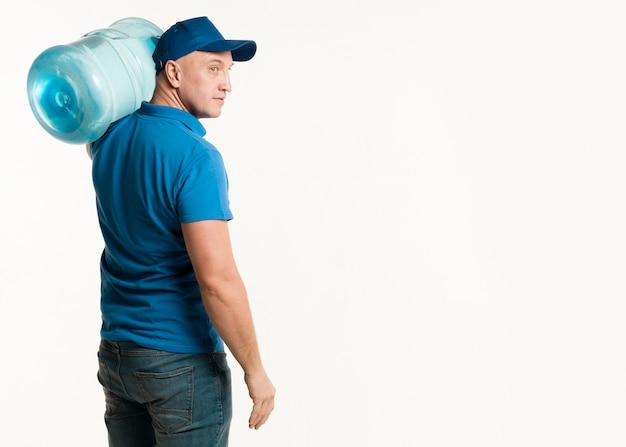 Vue Latérale Du Livreur Transportant Une Bouteille D'eau Photo gratuit