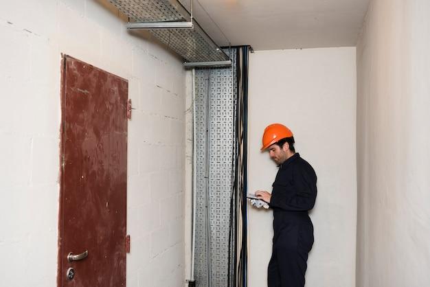 Vue Latérale Du Mâle électricien à L'aide De Téléphone Portable Au Travail Photo gratuit