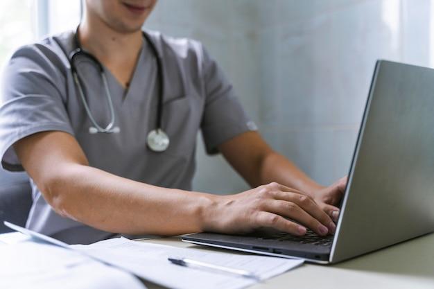 Vue Latérale Du Médecin Avec Stéthoscope Travaillant Sur Ordinateur Portable Photo gratuit